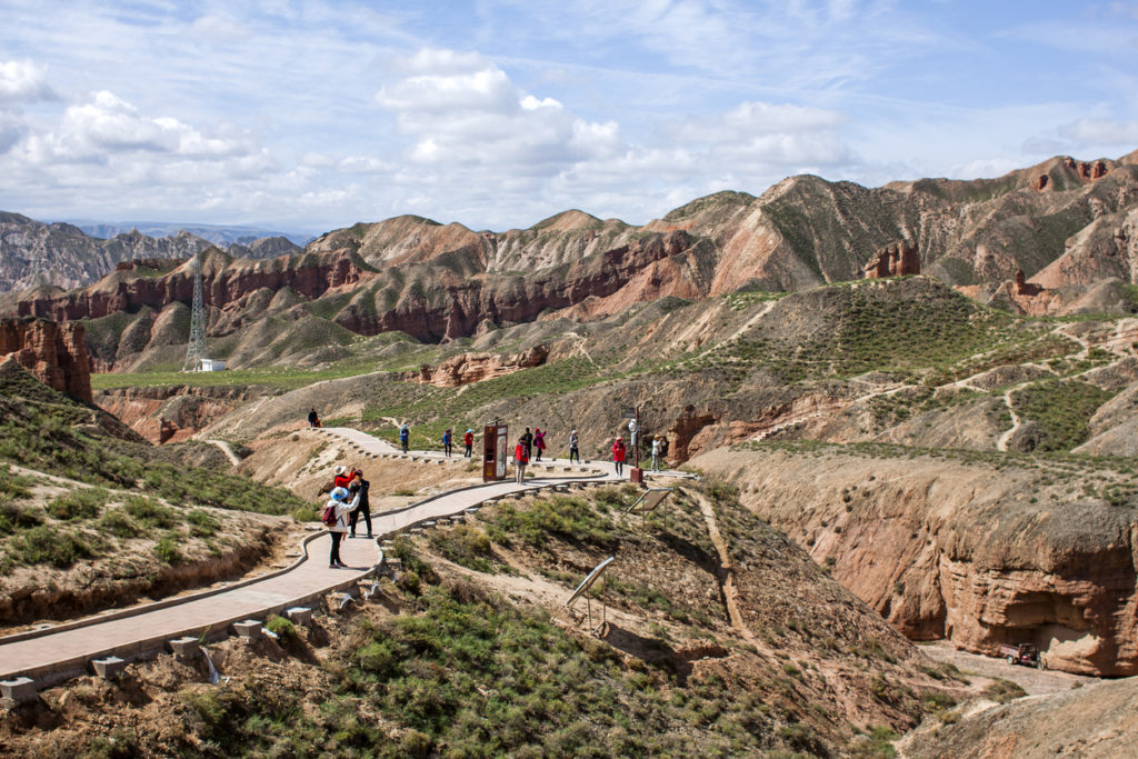 Group of Chinese Tourists are Walking Along a Path in Binggou Danxia Canyon Landform in Zhangye, Sunan Region, Gansu Province, China. Red Sandstone Rocks in the Geopark. Clouds and Blue Sky on a Sunny Day.